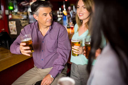beer after work: Attractive colleagues talking and drinking beer at the bar LANG_EVOIMAGES
