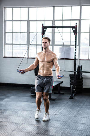 skipping rope: Fit man using skipping rope at crossfit gym