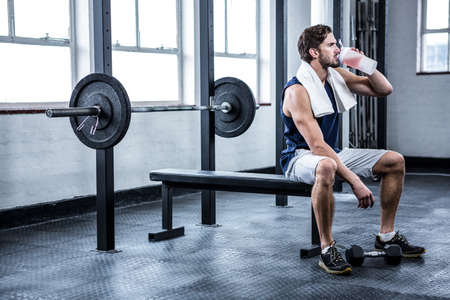 Fit man drinking his protein shake at crossfit gym LANG_EVOIMAGES