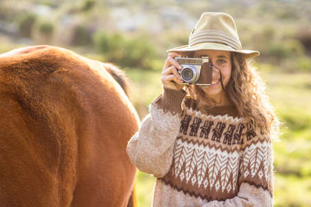 reigns: Young woman with her horse taking photo in the countryside