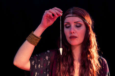 pendulum: Fortune teller holding pendulum with eyes closed while sitting at table LANG_EVOIMAGES