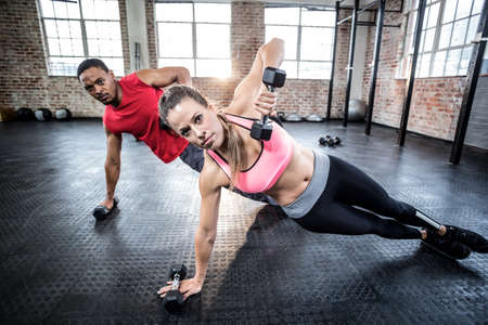 push ups: Fit couple doing push ups with dumbbells in crossfit gym