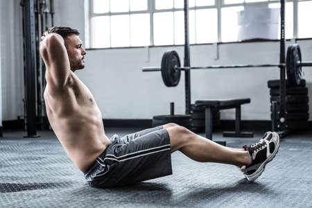 sit up: Fit shirtless man doing sit ups at crossfit gym
