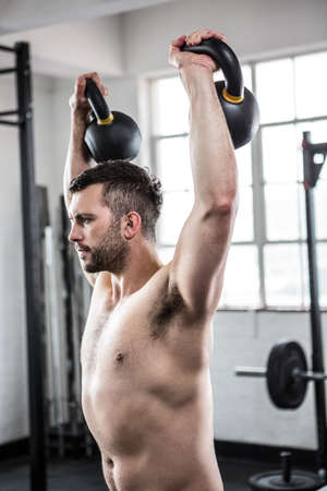 man working out: Fit shirtless man working out with kettlebells at crossfit gym LANG_EVOIMAGES
