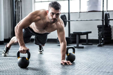 Fit shirtless man working out with kettlebells at crossfit gym LANG_EVOIMAGES