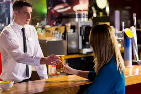 drinks after work: Handsome bartender serving cocktail to gorgeous woman in a bar