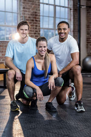crouching: Smiling woman crouching with trainers in crossfit gym