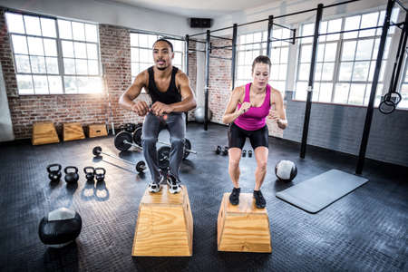 squatting: Fit couple doing squatting on boxes in crossfit gym LANG_EVOIMAGES