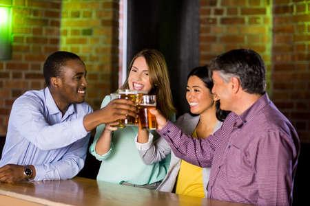 beer after work: Smiling colleagues having a drink together at the bar LANG_EVOIMAGES