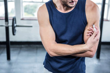 steroids: Fit man injecting steroids to arm at crossfit gym