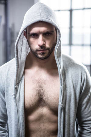 hooded: Fit man with hooded jumper at crossfit gym LANG_EVOIMAGES