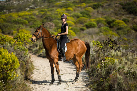 reigns: Young woman riding her horse in the countryside LANG_EVOIMAGES