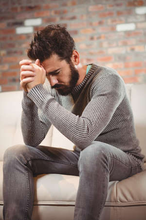 clasped: Worried man with hands clasped at home LANG_EVOIMAGES