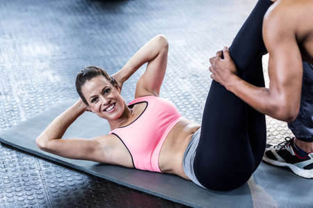 crunches: Woman doing stomach crunches on exercise mat in crossfit gym LANG_EVOIMAGES