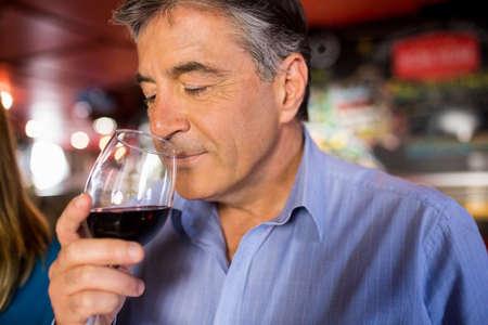 grey hair: Man with grey hair drinking wine at the bar