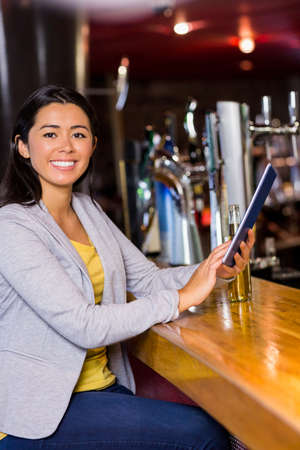 beer after work: Businesswoman using tablet and drinking beer at the bar