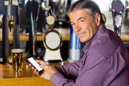 grey hair: Man with grey hair using mobile phone in the pub LANG_EVOIMAGES