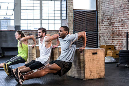 reverse: Fit people doing reverse push ups at crossfit gym LANG_EVOIMAGES