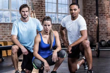 crouching: Serious woman crouching with trainers in crossfit gym LANG_EVOIMAGES