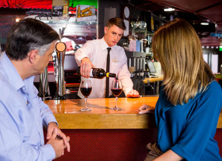 drinks after work: Bartender offering glasses of wine to couple at the bar counter