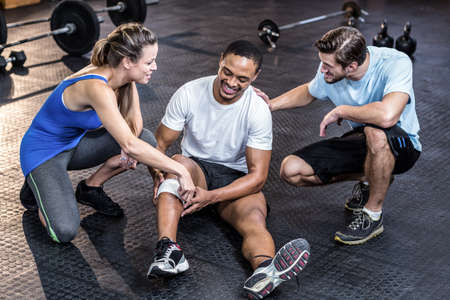 sports club: Sporty man having a muscle injury in crossfit gym LANG_EVOIMAGES