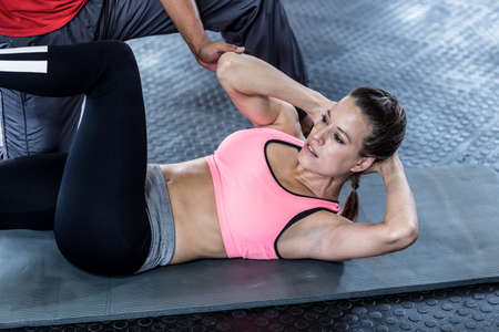 crunches: Male trainer assisting woman with abdominal crunches in crossfit gym LANG_EVOIMAGES