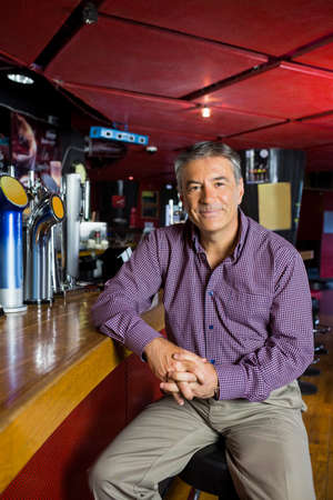 grey hair: Man with grey hair sitting in counter of the bar LANG_EVOIMAGES