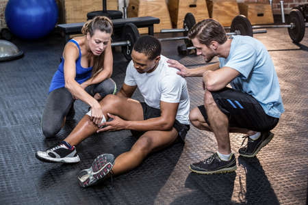 Fit man with a knee injury in studio at crossfit gym