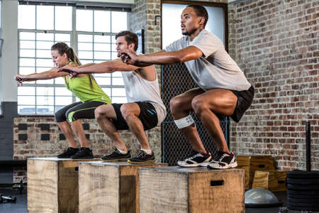 Fit people doing squat jumps at crossfit gym