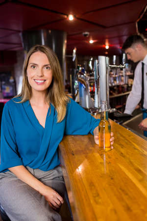 beer after work: Smiling woman having a drink at the bar
