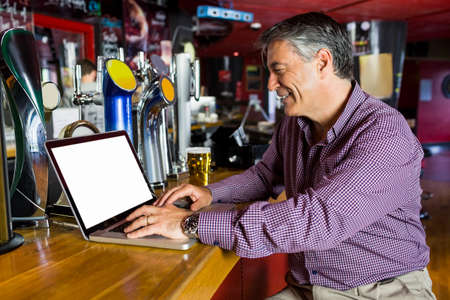 grey hair: Man with grey hair using his laptop on the counter