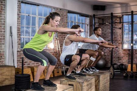 cuclillas: Tres atletas aptos cuclillas juntos en el gimnasio de crossfit