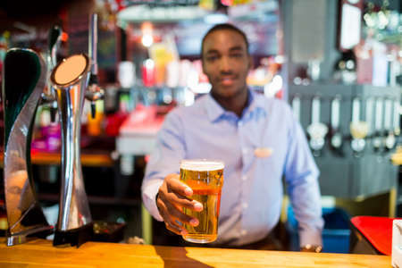 uniform attire: Glass of beer served by barkeeper in pub