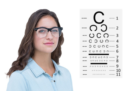 geeky: Pretty geeky hipster looking at camera against eye test Stock Photo