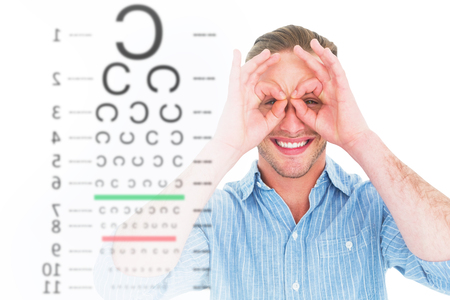 forming: Smiling doctor forming eyeglasses with his hands against eye test Stock Photo