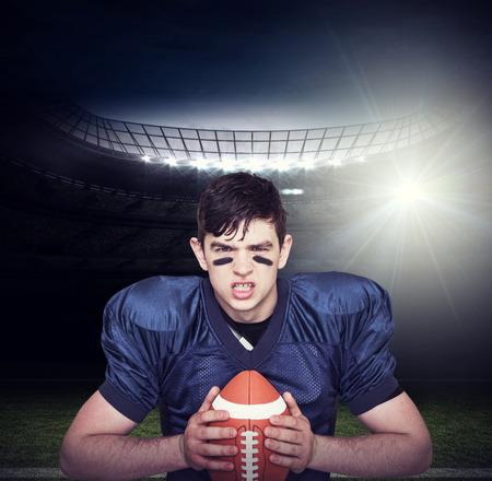 enraged: Enraged american football player holding a ball against american football arena Stock Photo