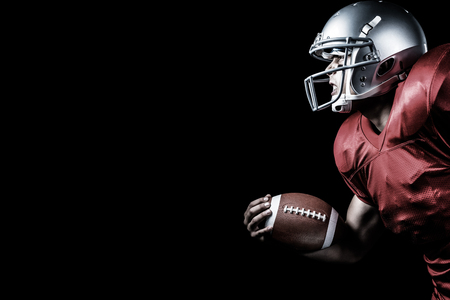 american football ball: Side view of aggressive sportsman playing American football against black Stock Photo