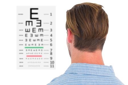eye test: Focused man in suit on eye test letters against eye test