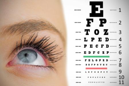 eye test: Close up of female blue eye against eye test Stock Photo