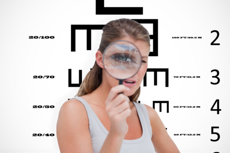 sense of sight: Young woman looking through a magnifying glass against eye test