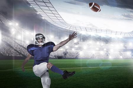 kicking: American football player kicking against rugby stadium
