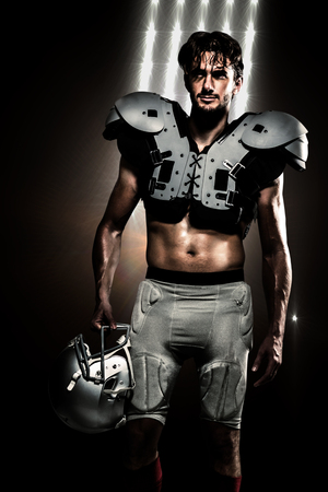 padding: Shirtless American football player with padding holding helmet against spotlights