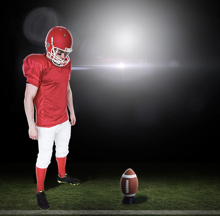 unsmiling: Unsmiling american football player looking down against lens flare