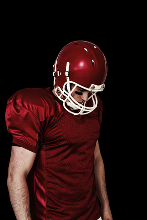 unsmiling: Unsmiling american football player looking down against black Stock Photo