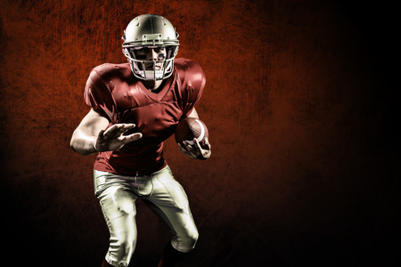 Portrait of defensive sportsman holding American football against dark background