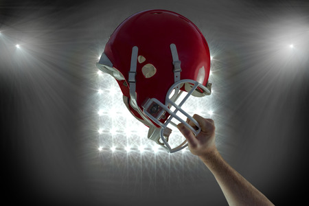 holding up: American football player holding up his helmet against spotlight Stock Photo