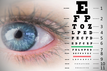 beautiful eye: Close up of female blue eye against eye test Stock Photo