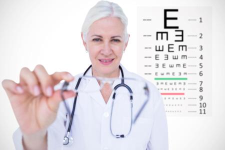 eye test: Smiling female doctor presenting eye glasses against eye test Stock Photo