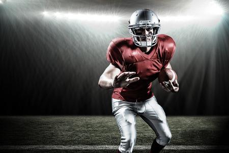 Portrait of defensive sportsman holding American football against spotlight
