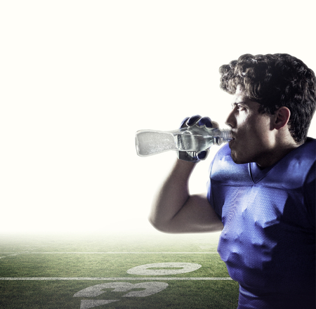 football pitch: Side view of sportsman drinking water against american football pitch